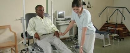 Female intern from Projects Abroad giving phsyiotherapy to a local man during her physiotherapy work experience in Ghana.